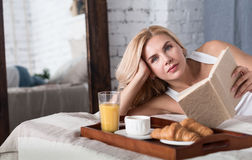Nice blond woman lying on bed with book Royalty Free Stock Photography