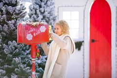 Nice blonde curly girl with letter near the Santa`s mailbox.  royalty free stock photos
