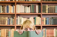 Nice blonde girl hiding behind a book. A shot of nice blonde girl hiding behind a book with bookshelf in the background Royalty Free Stock Photography