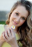 Nice blonde girl holding a daisy Royalty Free Stock Photo