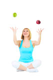 Nice blonde juggles apples. Nice blonde sits in a pose of a lotus and juggles red and green apples, isolated over white Stock Images