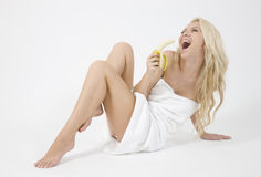 Nice blonde woman holding banana. On white background Royalty Free Stock Photography