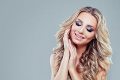 Nice blonde woman with long curly hair and makeup. On blue background royalty free stock images