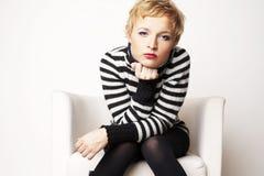 Nice blondgirl op de stoel Stock Foto