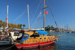 NIce boat in the harbor of Bodrum with view to St. Peter Castle. Nice wooden boat in the harbor of Bodrum with view to St. Peter Castle Royalty Free Stock Photos