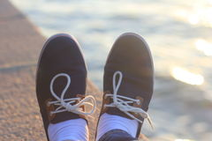 Relaxing on the waterfront. Of Moscow river stretching legs with the pair of nice shoes Royalty Free Stock Photography