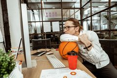 Nice bored man wanting to rest from work. Office routine. Nice bored man sitting with a ball while wanting to rest from work stock image