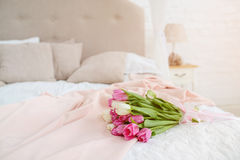 Nice bouquet with pink and white tulips on bed. Nice bouquet with pink and white tulips lie on bed in the light room at the morning stock photo