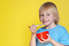 Nice boy with a bowl of corn-flakes Stock Photos