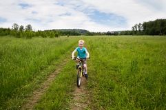 Nice boy cycling in the field. Country, non-urban, Russia Stock Images
