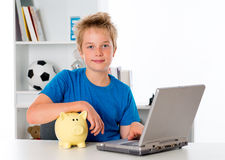 Nice boy with laptop and piggy bank Stock Images