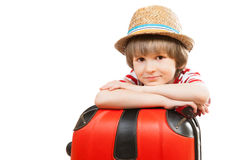 Nice boy leans elbow on a red suitcase. Isolated against white background Stock Photos