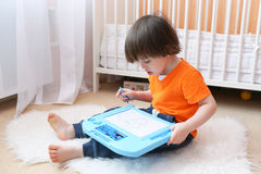 Nice boy in orange t-shirt paints on magnetic tablet at home Stock Photos