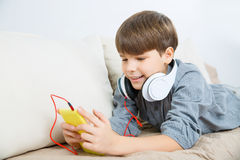 Nice boy relaxing on the sofa with phone and headset. Royalty Free Stock Photo