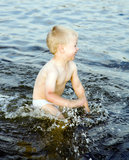 Nice boy swashes in water of the Baltic sea Royalty Free Stock Images