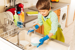 Nice boy wash dish in sink under water from tap. Little child boy cleaning and washing dishes in the kitchen sink under water from tap Royalty Free Stock Photography