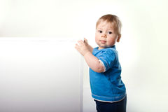 Nice boy beside a white blank for text or image Royalty Free Stock Image