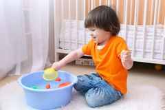 Nice boy (2,6 years) angles rubber fish and frogs in little basi Stock Photography