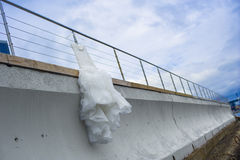Nice bridal dress is hanging on the pier fencing. Stock Photography