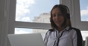 Nice brunette female student in headphone studying online, looking at laptop and talking. Smiling attractive woman conducting onli stock video footage