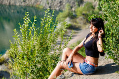 Nice brunette girl listening  music with headphones outdoors Stock Photography
