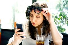 Nice brunette taking off glasses and looking at smartphone in a cafe Stock Photo
