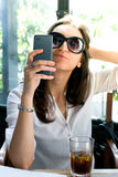 Nice brunette taking a selfie with her smartphone in a cafe Royalty Free Stock Images