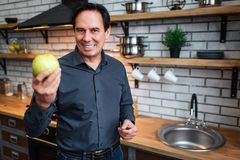 Nice businessman stand in kitchen and hold green apple. He look on camera and smile. Man stand alone. Nice businessman stand in kitchen and hold green apple. He stock images