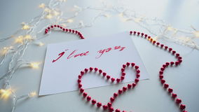 Nice calligraphic card with red inscription I love you on white sheet, on table with flickering garland and beads. Minimalistic postcard with text I love you stock footage