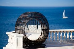 Calm down and relax. Nice calming photo of dark brown armchair with white pillows on the terrace with beautiful blue sea and small yacht behind. Scene of Royalty Free Stock Photography