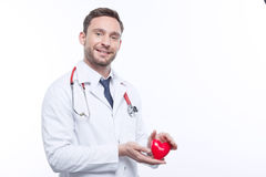 Nice cardiologist holding heart Royalty Free Stock Photography