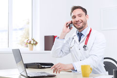 Nice cardiologist talking on the mobile phone Stock Images