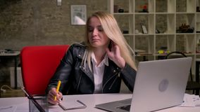 Nice caucasian blonde female is sitting at desktop and relaxing, having work break near her laptop and documents, light. Brick office on background stock video footage