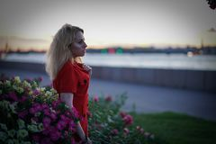 Nice caucasian girl walks late at night at sunset near the river alone stock image