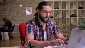 Nice caucasian guy with great black beard is typing on keyboard while being at his desktop and then looking with smirk. At camera, modern office nowadays stock video