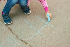Nice Caucasian Little Girl Draw Chalk on Asphalt Lines Blue Chalk Educative Parenting Activity for Children. copy space. stock photography