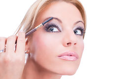 Nice caucasian model applying makeup with brush Stock Photo