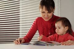 A nice Caucasian mom and daughter holding book Royalty Free Stock Image