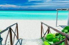 Nice charming view of tropical white sand beach and inviting tranquil, turquoise ocean on blue sky background Stock Images