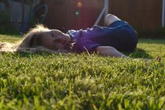 Beautiful young girl close up on  green grass in  summer. Smiling young face of girl stock photography