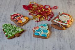 Nice Christmas sweets. Honey cookies in shape of Santa, snowman, pine tree and penguin laying near decoration beads on light woode Stock Photo