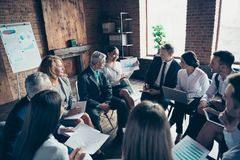 Nice classy stylish sharks experts professional ceo boss chief sitting on chairs in circle discussing financial plan. Result conference at modern industrial royalty free stock image
