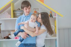 Nice close-knit family of mom, dad and daughter posing in their white room royalty free stock photos