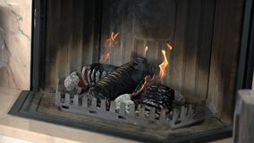 Nice close shot of a fireplace with burning logs. We see a process of making the briquettes out of wood and using them to blaze up the fire in fireplace stock video