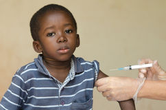 White doctor giving black African boy a needle injection as a vaccination. A nice close-up of a little black African ethnicity boy getting a medical injection as Royalty Free Stock Photos
