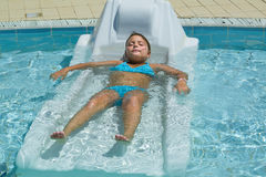 Nice closeup view of a pretty charming  little girl taking sunbath and relaxing in outdoor spa swimming pool bed Royalty Free Stock Photo