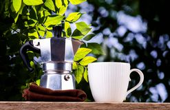 Nice coffee cup and coffee pot with green leaf and sun light background stock photos