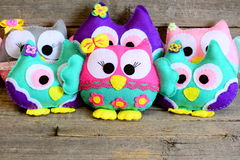 Nice colorful owls toys. Stuffed kids toys on vintage wooden background. Easy crafts made from felt Stock Image