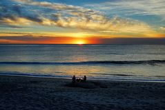 A couple and their dog sitting at the beach enjoying a sunset along the Orange County coast. Nice colorful partly cloudy sky with a wave rolling through on a Stock Images