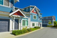 Row of new residential townhouse with entrance and garage doors on sunny day royalty free stock photo